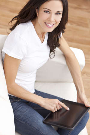 Beautiful young brunette woman at home sitting on sofa or settee using her tablet computer or iPad and smiling