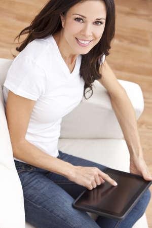 ojos marrones: Hermosa joven Morena en casa sentado en el sofá o canape con su tablet PC o iPad y sonriente