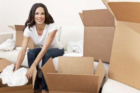 cajas de carton: Una hermosa sola joven desembalaje de cajas y pasar a una nueva casa.