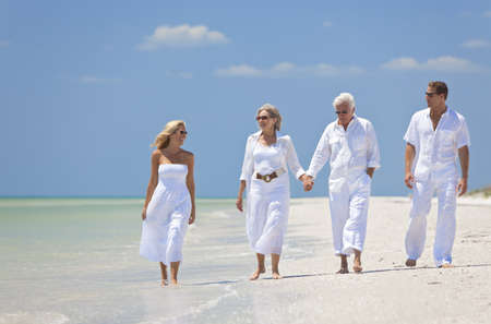 Two couples, generations of a family together walking and holding hands on a tropical beach