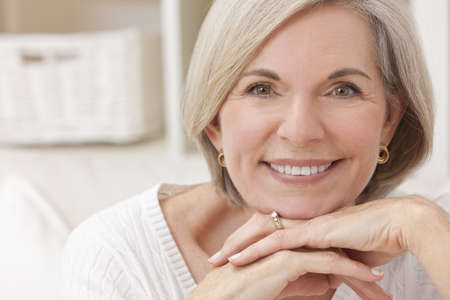 perfect teeth: Portrait of an attractive elegant senior woman relaxing at home. Stock Photo