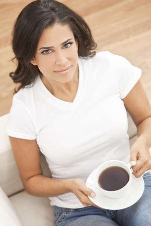 enigmatic: Una bella giovane donna Latina Ispanici o ragazza con un sorriso enigmatico, bere t� o caff� da una tazza bianca a casa sul suo divano