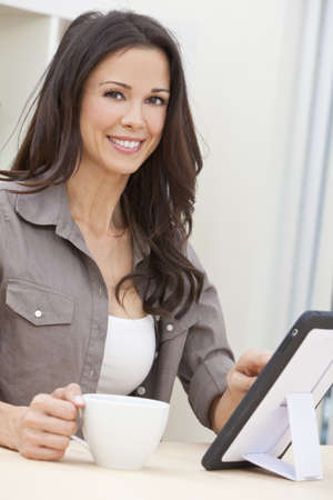 Beautiful, smiling, young brunette woman at home at a table using her tablet computer or iPad drinking a mug of tea or coffee Stock Photo - 10054678
