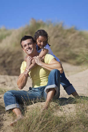 A man and young girl, father and mixed race daughter, playing and having fun in the sand dunes of a sunny beach photo