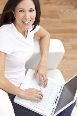 settee: Beautiful young brunette woman at home sitting on sofa or settee using her laptop computer and smiling