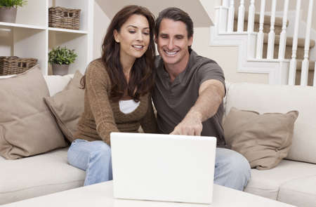 Attractive, successful and happy middle aged man and woman couple in their thirties, sitting together on sofa at home using a laptop computer. photo