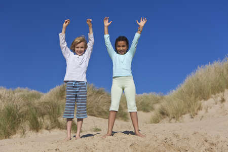 Mixed race African American girl child and blond boy playing and having fun in the sand dunes of a sunny beach photo