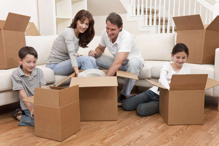 packing boxes: Family, parents, son and daughter, unpacking boxes and moving into a new home. Stock Photo