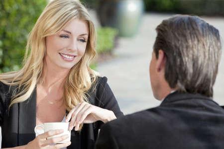 Una mujer joven hermosa y sofisticada con café en una mesa de café de la ciudad moderna con su amiga un empresario vestido inteligente