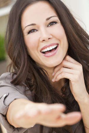 Portrait of a beautiful brunette young woman with perfect teeth smiling laughing and reaching to camera Stock Photo