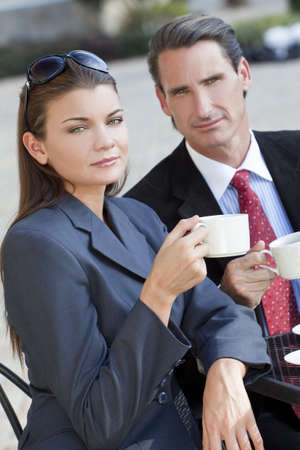 happy rich woman: A beautiful and sophisticated young woman having coffee at a modern city cafe table with her friend a smart dressed businessman