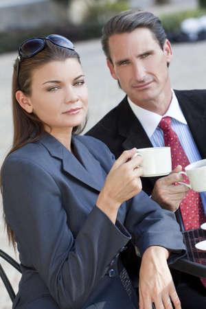 wealthy lifestyle: Una donna bella e sofisticata giovane, un caff� a un tavolo moderno bar della citt� con la sua amica un uomo d'affari astuto vestito Archivio Fotografico