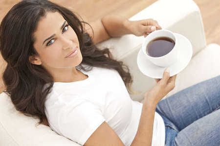 latina: A beautiful young Latina Hispanic woman or girl with a wonderful enigmatic smile drinking tea or coffee from a white cup at home on her sofa Stock Photo