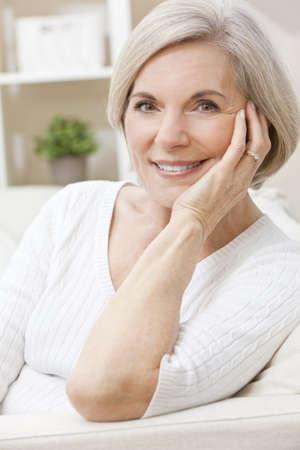 damas antiguas: Retrato de una elegante senior mujer atractiva relajante en casa feliz y sonriente. Foto de archivo