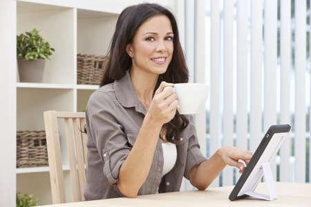Bella, sonriente, joven Morena mujer en su casa en una mesa con su tablet PC o iPad beber una taza de t� o caf�