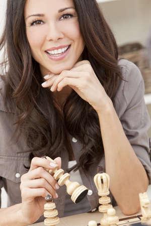 jugando ajedrez: Una hermosa mujer joven morena latina con un juego de ajedrez dentudo sonrisa maravillosa de jugar en casa