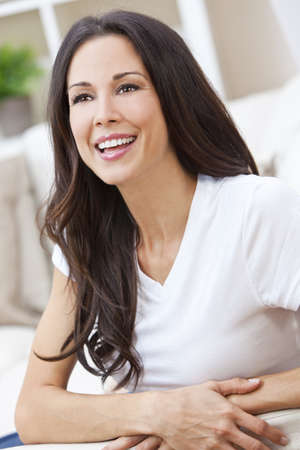 Portrait of a beautiful brunette young woman with perfect teeth smiling and relaxed photo