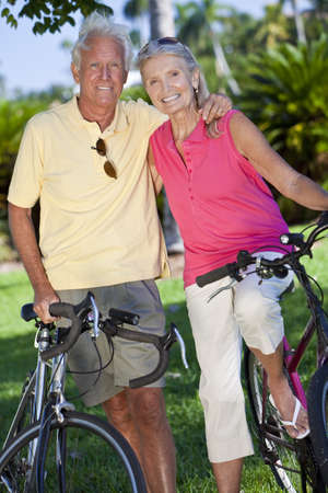Happy senior man and woman couple together cycling on bicycles in a park Stock Photo - 10708219