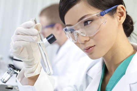 clinical: A Chinese Asian female medical or scientific researcher or doctor using looking at a test tube of clear liquid in a laboratory with her colleague out of focus behind her. Stock Photo