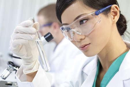 laboratorio clinico: Un chino, asi�tico, investigadora m�dica o cient�fica, o doctor con mirar a un tubo de ensayo de l�quido transparente en un laboratorio con su colega fuera de foco detr�s de ella. Foto de archivo