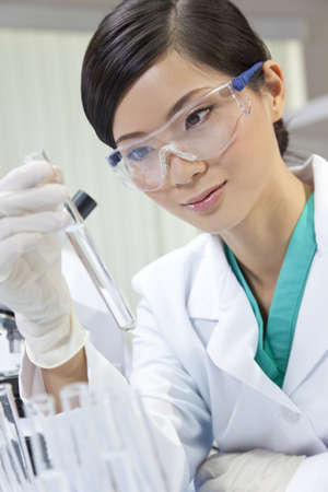 clinical research: A Chinese Asian female medical or scientific researcher or doctor using looking at a test tube of clear liquid in a laboratory with her colleague out of focus behind her. Stock Photo