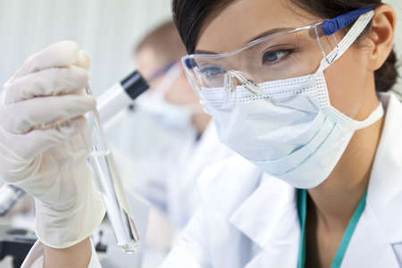 environmental science: A Chinese Asian female medical or scientific researcher or doctor using looking at a test tube of clear liquid in a laboratory with her colleague out of focus behind her. Stock Photo