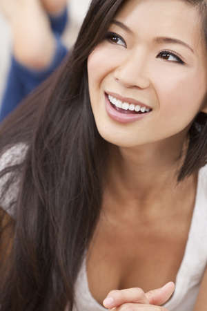 A beautiful sexy young Chinese Asian Oriental woman with a wonderful toothy smile laying down on a sofa and relaxing Stock Photo - 11043478