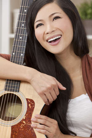 A beautiful happy young Chinese Asian Oriental woman with a wonderful toothy smile holding her guitar Stock Photo - 11043483