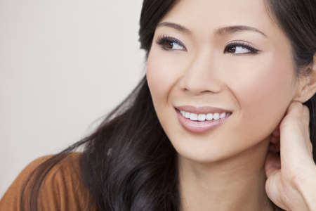 A beautiful young Chinese Asian Oriental woman with a wonderful toothy smile  Stock Photo - 11043476