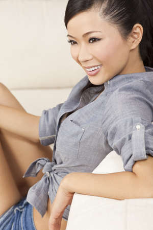 A beautiful sexy young Chinese Asian Oriental woman with a wonderful toothy smile relaxing on a sofa in denim jeans shorts photo