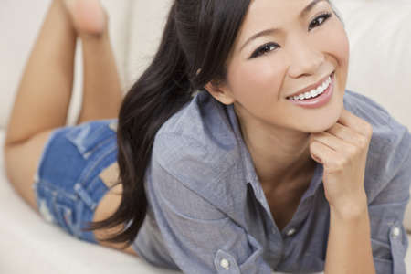 sexy asian girl: A beautiful sexy young Chinese Asian Oriental woman with a wonderful toothy smile laying down relaxing on a sofa in denim jeans shorts