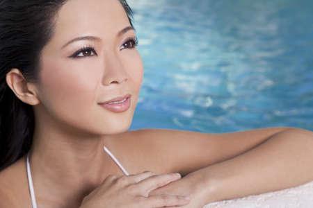 Una hermosa joven y sexy mujer oriental china de Asia con un bikini y relajante en el lado de una piscina.