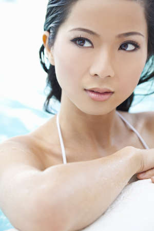 A beautiful sexy young Chinese Asian Oriental woman wearing a bikini and relaxing on the side of a swimming pool. Stock Photo - 11043469