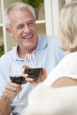 dating and romance: Happy senior man and woman couple sitting together at home smiling and drinking wine