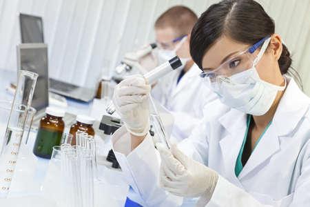 investigador cientifico: Un chino, asi�tico, investigadora m�dica o cient�fica, o doctor con mirar a un tubo de ensayo de l�quido transparente en un laboratorio con su colega fuera de foco detr�s de ella. Foto de archivo