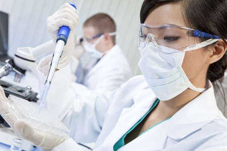 clinical: A Chinese Asian female medical or scientific researcher or doctor using a pipette and cell tray in a laboratory with her colleague out of focus behind her. Stock Photo