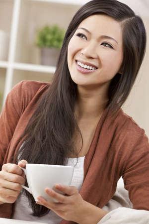 dentudo: Una hermosa joven feliz chinos mujer asi�tica oriental, con un maravilloso t� dentudo sonrisa o beber caf�