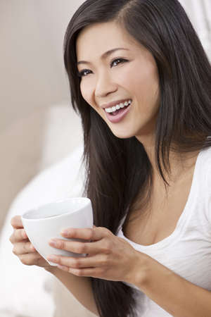 A beautiful happy young Chinese Asian Oriental woman with a wonderful toothy smile drinking tea or coffee photo