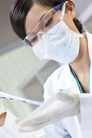 A Chinese Asian female medical or scientific researcher or doctor using a pipette and cell tray in a laboratory photo