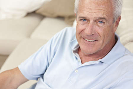 gray eyes: Happy and healthy senior man sitting on a sofa at home smiling and happy Stock Photo