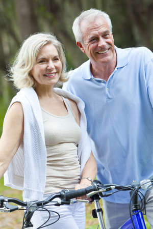 Happy senior man and woman couple sitting together smiling and happy with bicycles at a park photo