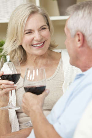 Happy senior man and woman couple sitting together at home smiling and drinking wine photo