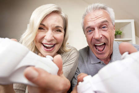 Senior couple, man and woman, laughing & having fun playing video console games together. Stock Photo - 11059176
