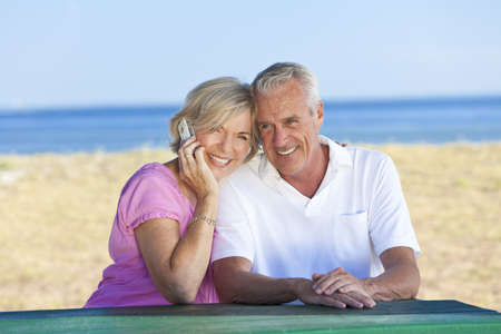 old cell phone: Happy senior man and woman couple sitting together at a table by a beach talking on a cell phone