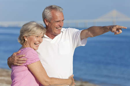 Happy senior man and woman couple together walking and pointing on a deserted beach  photo