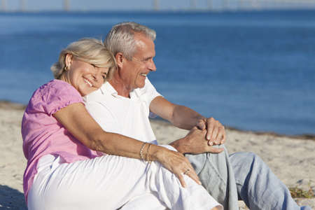 Happy romantic senior man and woman couple together on a deserted beach  photo