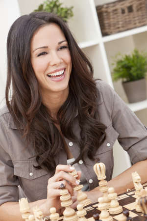 Portrait of a beautiful brunette young woman with perfect teeth smiling and laughing whilst playing chess photo