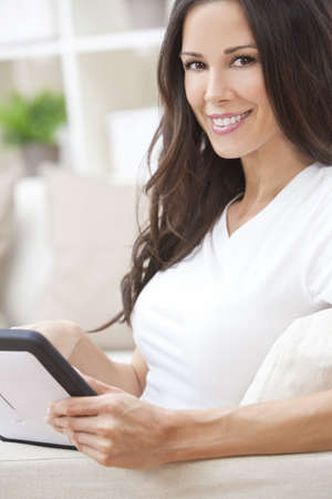 Beautiful young brunette woman at home sitting on sofa or settee using her tablet computer and smiling