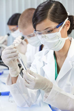 lab test: A Chinese Asian female medical or scientific researcher or doctor using looking at a test tube of clear liquid in a laboratory with her colleagues out of focus behind her.