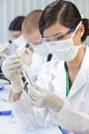 laboratorio clinico: Un chino, asi�tico, investigadora m�dica o cient�fica, o doctor con mirar a un tubo de ensayo de l�quido transparente en un laboratorio con sus colegas fuera de foco detr�s de ella.